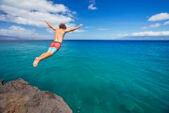 Man jumping off cliff into the ocean Stock Photos