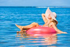 woman floating on raft in tropical ocean - stock photo