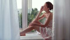 Young beautiful woman with a smart-phone  on the window-sill Stock Footage