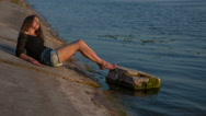 Beautiful girl in short shorts lying near the water Stock Footage