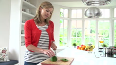 Woman Chopping Peppers On Wooden Board - stock footage