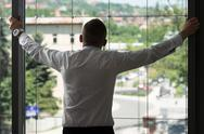 Businessman looking through office window Stock Photos