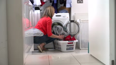 Woman Loading Clothes Into Washing Machine Stock Footage