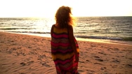 Stock Video Footage of Young Woman Walking on Beach under Sunset Light. Slow Motion.