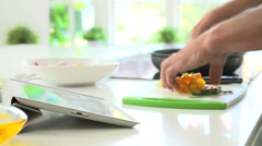 Close Up Of Man Following Recipe On Digital Tablet Stock Footage