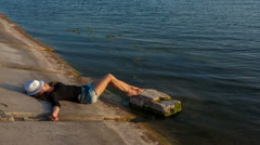 Woman in hat and short shorts lying near the water Stock Footage