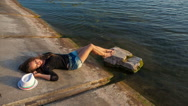 Luxurious young girl in short shorts lying near the water Stock Footage