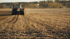 Tractor working in the grain fields - driving towards camera - stock footage