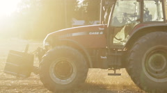 Tractor working in the grain fields in slow motion - lens flare and sunset - stock footage