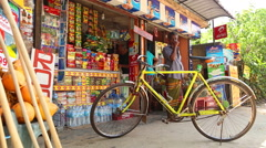 Bike parked outside a shop with man standing in background in Mirissa. Stock Footage