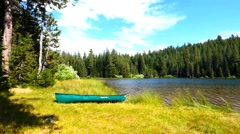 Canoe on the Shore of a Tranquil Alpine Lake Stock Footage