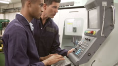 Engineer Teaching Apprentice To Use Computerized Lathe Stock Footage