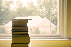 Stack of Books in Front of Window Stock Photos