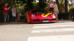 Red McLaren F1 driving by Stock Footage