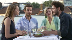 Group Of Friends Eating Meal On Rooftop Terrace Stock Footage