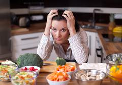 depressed and sad woman in kitchen - stock photo