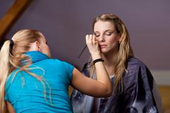 make-up session - two young women - stock photo