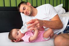 Portrait of father feeding daughter Stock Photos