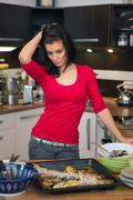 unhappy woman standing in kitchen - stock photo