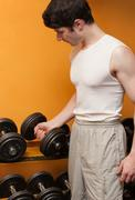 Young man take dumbbells in sport club Stock Photos