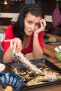 tired woman cleans up leftovers from lunch - stock photo