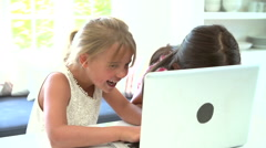 Two Young Girls Using Laptop At Home And Whispering Stock Footage