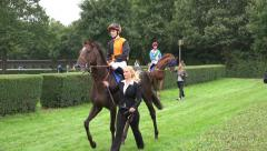 4k Jockeys and racing horses leaded by staff to the course Stock Footage