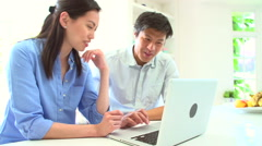 Asian Couple Looking at Laptop In Kitchen Stock Footage