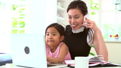 Busy Mother Working From Home With Daughter Stock Footage
