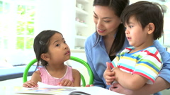 Asian Mother Reading A Story To Children Stock Footage