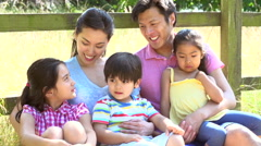 Asian Family Relaxing By Fence On Walk In Countryside - stock footage
