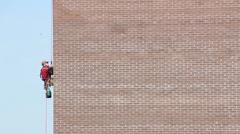 Steeplejack Builder worker plastering industrial building facade Stock Footage