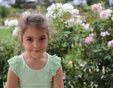 Smiling little girl and flowers Stock Photos