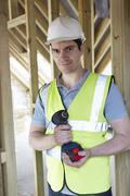 builder on construction site holding cordless drill - stock photo