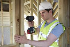 Stock Photo of construction worker using cordless drill on house build