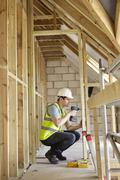 Construction worker using drill on house build Stock Photos