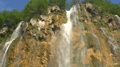 Slow motion tilt with water falling down a waterfall Stock Footage