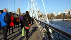 London pedestrians walk on bridge over River Thames - dolly Stock Footage