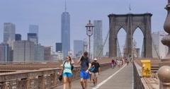 4K Tourists Walk Across the Brooklyn Bridge as Bikers Pass By Stock Footage