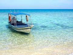 Boat Floating on Turquoise Colored Waters of Tropical Island Stock Photos