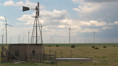 Old irrigation windmill and wind turbines share the sky and prairie of Colorado. Stock Footage