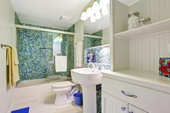 refreshing white bathroom with aqua tile wall trim - stock photo