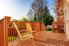 cozy small backyard with wooden walkout deck - stock photo
