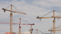 Heavy construction machinery, cranes inside site, modern residential structure - stock footage