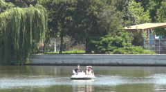Two people in waterbuggy, using pedals for moving faster, relaxing in park lake Stock Footage