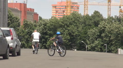 Father and son riding bikes in weekend, sport activity in family, using a track Stock Footage