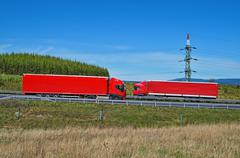 Spring landscape with highway and oncoming red trucks passing around pylon Kuvituskuvat