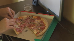 Unhealthy lifestyle young man eating pizza and drinking beer staying at computer Stock Footage