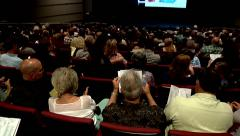 crowd audience of people sitting in a theater lifestyle entertainment cutaway Stock Footage