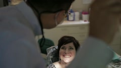 Orthodontist looks at patient's smile - stock footage